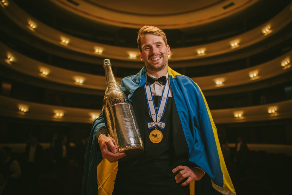 Arvid Rosenberg draped in a Swedish flag on the stage at the final of the Best Sommelier in the World competition