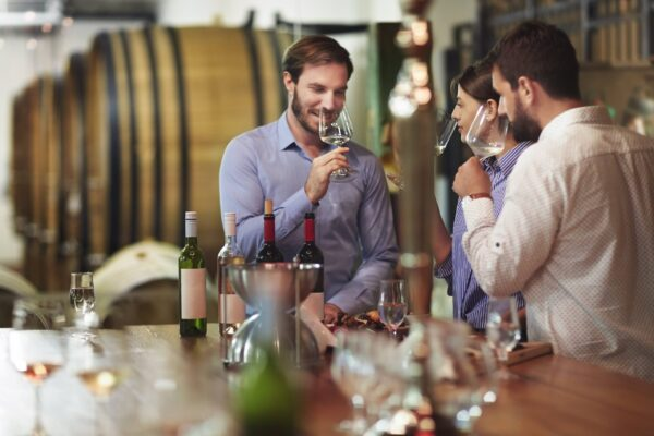 Heterosexual couple tasting white wine in the winery during degustation.