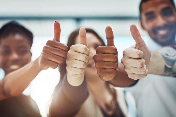 Cropped shot of a team of colleagues showing thumbs up at work
