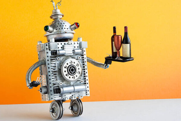 Restaurant automation service concept. Robot waiter serving a tray with a bottles and wine glass. Two wheels robotic character on yellow wall, gray floor background. copy space.